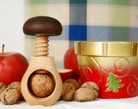 Wooden nutcracker, nuts, bowl and apples Stock Photos