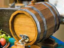 Wooden oak wine barrel with metal tap. Royalty Free Stock Images
