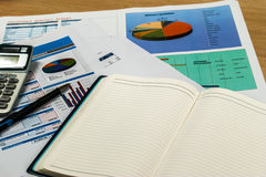 Wooden office desk with open diary book and data chart Royalty Free Stock Photo