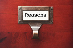 Wooden Office File Cabinet with Reasons Label. Lustrous Wooden Cabinet with Reasons File Label in Dramatic LIght Stock Photography