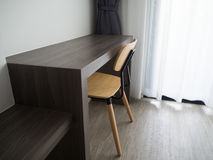 Wooden office table with modern chair and blurry beautiful white Stock Image