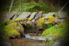 Wooden old bridge on mountain stream Stock Photo