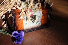 Wooden old chest casket jewelry box with painting with a bouquet of dry cereals and blue flowerswn. Wooden old box with painting with a bouquet of dry cereals stock photos