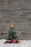 Wooden old country style background with a green christmas tree. Wooden old country background with a green christmas tree and a red gift box with checked ribbon Stock Photo