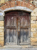 Wooden old door of stone house. Unstripped wooden old door of stone house Stock Images