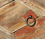 Wooden old fence with an iron grip. Metal circle on a rustic door. Retro and vintage royalty free stock photography