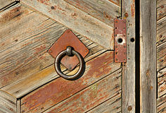 Wooden old fence with an iron grip. Metal circle on a rustic door. Retro and vintage stock photography