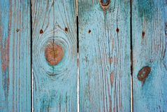 Wooden old fence surface painted with turquoise shabby paint and rusty nails. Grunge background texture royalty free stock photo