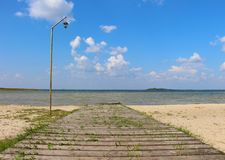 Wooden old ferny pier with vintage lamppost near the lake against blue summer sky. Without people stock images