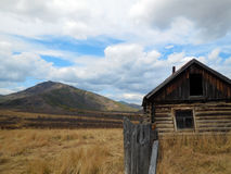 Wooden old hunting house in the forest on a background of mountains and sky in the Mountain Altai. Royalty Free Stock Photo
