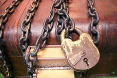 Wooden, old, old brown chest locked to a large lock tied with thick, strong metal chains. Stock Photo