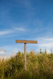 Wooden old road sign pole and blue sky. With clouds on background with green grass Royalty Free Stock Images