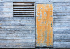 Wooden old weather-beaten barn with a yellow old door. Yellow old door and a window with a wooden grate on the facade of a wooden old gray weather-beaten barn Stock Photos