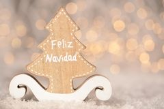 Wooden ornament cutout in the shape of a pine tree - translation text Feliz Navidad - merry christmas. Wooden ornament cutout in the shape of a pine tree with royalty free stock photography