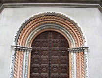 Wooden ornate baroque gate. Wooden door with huge nails and interesting bas-relief carvings on a facade of a baroque basilica in Bergamo, Lombardy, Italy Stock Photos