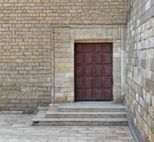 Wooden ornate engraved red door on bricks stone wall and deck stairs Stock Images