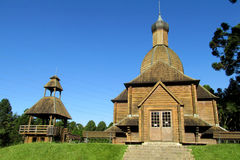 Wooden orthodox church. Among green grass and orange flowers. Ukrainian church in park of Curitiba city, Parana state, Brazil Stock Photography