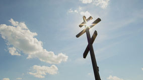 Wooden orthodox Cross in front of blue sky. Telephoto Royalty Free Stock Images