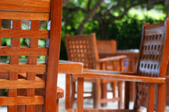Wooden outdoor cafe chairs. Wooden outdoor chairs in cafe or restaurant, leafy green background Royalty Free Stock Image