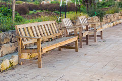 Wooden outdoor furniture. Lounge chairs in hotel garden invite you to relax Stock Photography