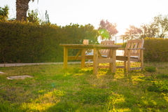 Wooden outdoor furniture. Lounge chairs in hotel garden invite you to relax Royalty Free Stock Images
