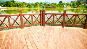 Wooden outdoor patio wood deck. Empty exterior wood deck with balustrade. Outdoor wooden patio by lake in park stock photos