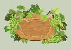 Wooden oval frame with green grapes and leaves  on beige Stock Images