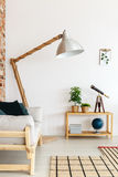 Oversize lamp in the corner. Wooden oversize lamp with wire standing in the corner of bright living room stock images