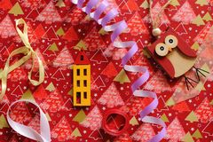 Wooden owl and house toy and violet serpantine with colorful ribbons on festive wrap as christmas and new year decoration. Wooden owl and house toy and violet Stock Photo