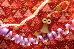 Wooden owl toy and violet serpantine with white ribbon on festive wrap as christmas and new year decoration. Bright holidays background. Merry Christmas Stock Photography