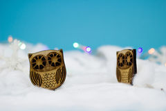 Wooden owls in snow. On blue background Royalty Free Stock Photos