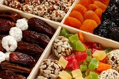 In the wooden package is dried apricots, peanuts, sesame, dried fruits, kumquat, plum stock image