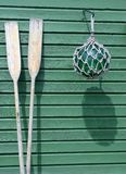 Wooden paddles and a buoy against a green wall Stock Images