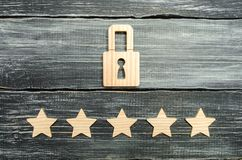 A wooden padlock and five stars. Security, security of users and business. Internet security, antivirus, data protection. Alarms o. F home, car and business. The stock photography