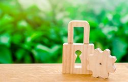 Wooden padlock and gear. Conceptual strength and security mechanisms and critical nodes. Protection against unauthorized access. Insurance and security of royalty free stock photo