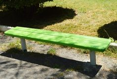 Wooden painted bench along the paths in the summer Park on a Sunny day.  stock photography