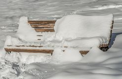 A wooden painted brown color beautiful bench with black wrought-iron legs stands with white snow in a park in winter royalty free stock images