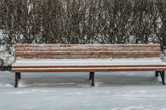 A wooden painted brown color beautiful bench with black wrought-iron legs stands with white snow in a park in winter stock photos