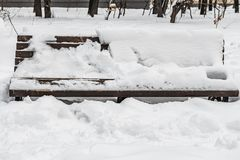 A wooden painted brown color beautiful bench with black wrought-iron legs stands with white snow in a park in winter stock photography