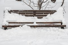 A wooden painted brown color beautiful bench with black wrought-iron legs stands with white snow in a park in winter stock image