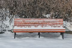 A wooden painted brown color beautiful bench with black wrought-iron legs stands with white snow in a park in winter. A wooden painted brown color beautiful stock photos