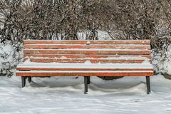 A wooden painted brown color beautiful bench with black wrought-iron legs stands with white snow in a park in winter. A wooden painted brown color beautiful stock image