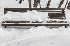 A wooden painted brown color beautiful bench with black wrought-iron legs stands with white snow in a park in winter royalty free stock image