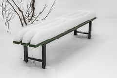 A wooden painted green color beautiful bench with black iron legs with white snow in a park in winter royalty free stock photos
