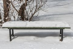A wooden painted green color beautiful bench with black iron legs with white snow in a park in winter royalty free stock photography