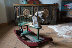 Wooden painted horse and a chest in a room Stock Images
