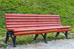 A wooden painted red color beautiful bench with black wrought-iron legs. Stands by the walkway in a park royalty free stock image