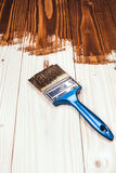 Wooden painting. Varnishing a wooden shelf using paintbrush Royalty Free Stock Photo
