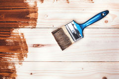 Wooden painting. Varnishing a wooden shelf using paintbrush Royalty Free Stock Photography