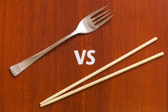 Wooden pairs of chopsticks vs fork. Abstract conceptual image Stock Images